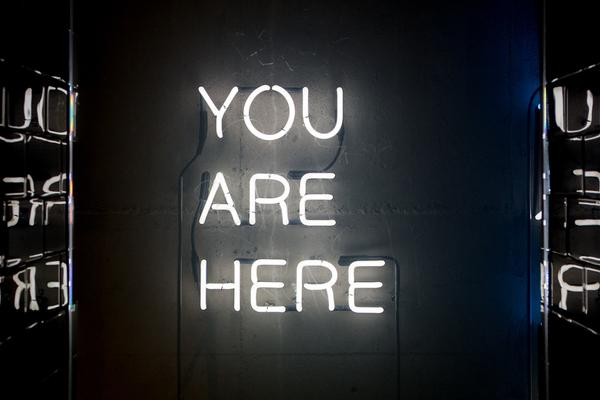 Neon letters spelling out the words 'you are here'